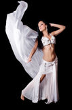 Belly Dancer Dancing with Flowing White Silk Veil. An exotic, brunette bellydancer dances with a flowing, white silk veil. Isolated on a black background Royalty Free Stock Photos