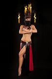 Belly Dancer with Fire Wands. Exotic belly dancer wearing a red and black costume with hijab and fire headdress and holding fire wands. Shot in the studio on an Stock Photo