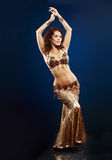 Belly dancer in gold. Beautiful professional belly dancer in gold costume Royalty Free Stock Photography