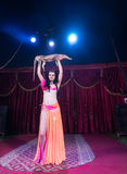 Belly Dancer Holding Alligator Above Head on Stage Stock Images