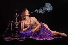 Belly dancer with hookah. A beautiful young belly dancer blows smoke from a hookah Royalty Free Stock Photography