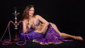 Belly dancer with hookah. A beautiful young belly dancer poses seductively with a hookah Stock Image