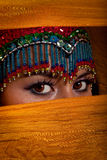 Belly dancer peeking from behind veil. Attractive and exotic belly dancer wearing a head dress and peeking from behind an orange veil Stock Images