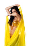 Belly dancer posing with a bright yellow silk veil Stock Photo