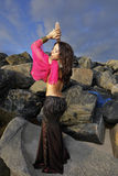 Belly dancer posing on the rocks Stock Photography