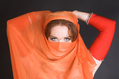 Belly Dancer in Red. Blue eyed belly dancer with a brightly colored scarf stock images