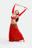 Belly dancer in red. Beautiful belly dancer in red outfit holding sword, isolated Stock Photography