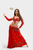 Belly dancer in red. Beautiful belly dancer in red outfit with sword on her head, isolated Stock Images