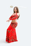 Belly dancer in red. Beautiful belly dancer in red outfit balancing sword, isolated Royalty Free Stock Photo