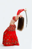 Belly dancer in red. Beautiful belly dancer in red outfit holding sword hanging backward, isolated Royalty Free Stock Photo