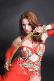 Belly Dancer with sword. Belly dancer with tribal sword decorated in gold stock image