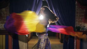 Belly Dancer with two colored veils waving at the concert in a cafe. Young beautiful woman with dark long hair smiling and spreads in all directions bright stock footage
