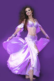 Belly dancer in violet costume. Active young woman Royalty Free Stock Photos
