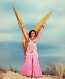 Belly dancer with wings performing on the beach Royalty Free Stock Photo