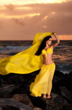 Belly Dancer in Yellow Costume on the Beach at Sunrise Royalty Free Stock Photo