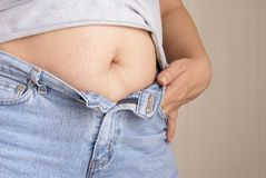 Belly Fat. Ugly Belly Fat. Woman's fat belly is hanging out of unbutton blue jeans Royalty Free Stock Photo