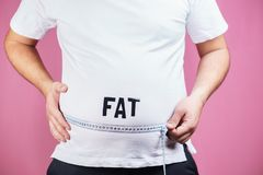 Belly fat, glutton. Fat man with measure tape. Overeating, diet, glutton, diabetes, junk food. fat obese man with big belly and measuring tape stock photo