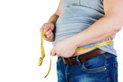 The belly of a fat man isolated on white background. Fat man hol. Ding a measuring tape. Weight Loss Stock Images