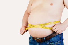 The belly of a fat man isolated on white background. Fat man hol. Ding a measuring tape. Weight Loss Stock Photography