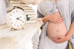 Belly hugging his arms on the background of an alarm clock and b Royalty Free Stock Photography