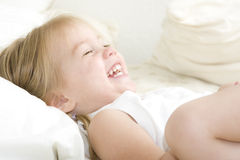 Belly Laugh. Happy little girl on bed laughing so hard her eyes are shut Royalty Free Stock Photos