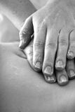 Belly massage. Massage therapist hands on client's belly; monochrome Royalty Free Stock Photography