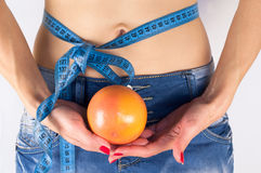 Belly and Orange. Woman holds an orange in front of her naked belly with tape measure tied around it on white background royalty free stock photos