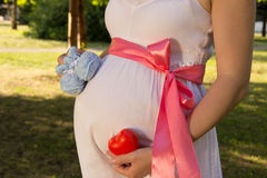 Belly of pregnant girl in white summer dress in park with booties, red ribbon on belt and heart and clock on hands. Belly of pregnant girl in white summer dress royalty free stock photos
