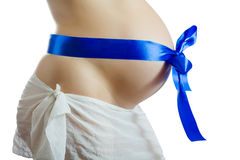 Belly of pregnant woman with blue ribbon Stock Photos