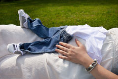 Belly of a pregnant woman holding baby clothes close-up Royalty Free Stock Images