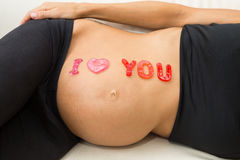 On the belly of a pregnant woman is I love you Royalty Free Stock Photo