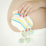 Belly of pregnant woman with knitted socks Royalty Free Stock Photography