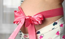 Belly of pregnant woman. Belly of pregnant woman with pink bowknot royalty free stock photography