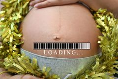Belly of pregnant women and loading text in concept of time in c Royalty Free Stock Images