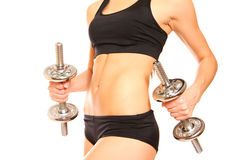 Belly of slim woman with two dumbbells on a white background Royalty Free Stock Photos