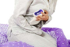 Bellyache. Woman sitting on the bed with hot water bottle royalty free stock photo