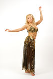 Bellydancer. Oriental dancer posing in golden-black costume Royalty Free Stock Photo