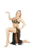 Bellydancer. Beautiful blond bellydancer in golden-black costume standing on the knee Stock Photography