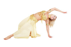 Bellydancer. Belly-dancer in golden costume making acrobatic element Royalty Free Stock Photos