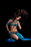 Bellydancer doing a Hair Toss. A beautiful, exotic bellydancer doing a hair toss wearing a teal and royal blue costume. Shot in the studio on a black background Stock Photo