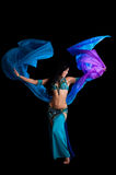 Bellydancer with Flowing Blue Veil. An exotic belly dancer wearing a teal and royal blue costume. She is dancing with a flowing blue and purple silk veil. Shot Royalty Free Stock Images