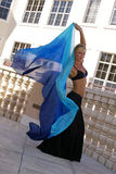 Bellydancer with veil. Beautiful blonde belly dancer with veil on balcony outside buildings Royalty Free Stock Image
