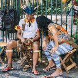Brazilian indigenous man on his cell phone. Belo Horizonte, Brazil - Dec 24, 2017: Brazilian indigenous Tupi or Tapuia man dressed in a traditional costume looks Stock Image