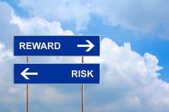 Belohnung und Risiko auf blauem Verkehrsschild Stockbild