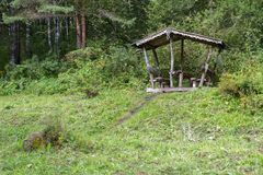 Beautiful wooden carved arbor on the terrenkur health trail along the Belokurikha mountain river. Belokurikha, Russia - July 30, 2015: Beautiful wooden carved Royalty Free Stock Photography