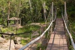 Wooden gazebo and suspension bridge across the Belokurikha mountain river on terrenkur health trail. Belokurikha, Russia - July 30, 2015: Wooden gazebo and Stock Photography