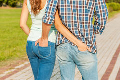 Belong to each other. Young loving couple holding their hands in the pockets of each others jeans while walking Royalty Free Stock Image