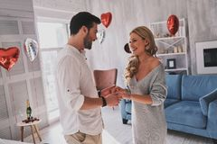 They belong together. Beautiful young couple holding hands and l. Ooking at each other with smile while standing in the bedroom full of balloons Stock Photography
