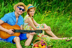 Beloved girlfriend. Enamored young men with a guitar singing his beloved girlfriend. They are sitting together on a lawn on a sunny summer day. Love concept Stock Photography