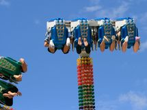 Below Amusement Ride. People on an amusement park ride stock photo
